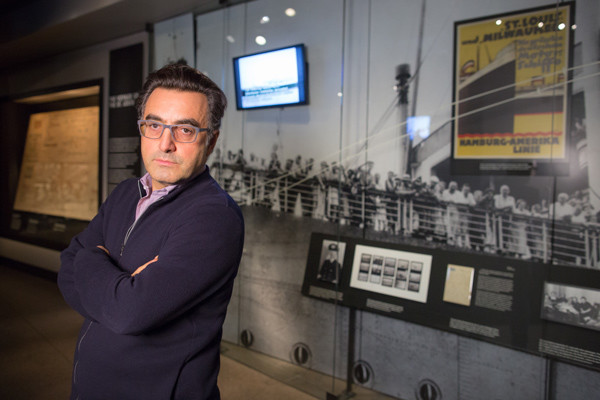 Maziar Bahari stands in front of a display in the Museum's Permanent Exhibition about the Jewish refugees aboard the MS St. Louis, the subject of his 1994 documentary. US Holocaust Memorial Museum