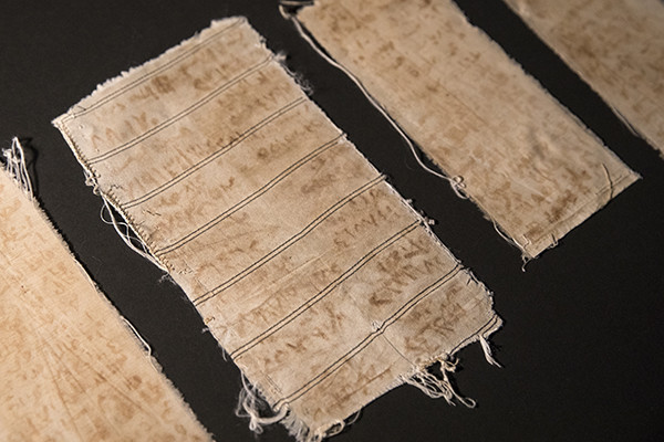 When Mansour Omari was released from prison in Syria, he smuggled out these scraps of cloth sewn within the shirt he was wearing. The names of his cellmates are written on them with an ink made from blood and rust. US Holocaust Memorial Museum