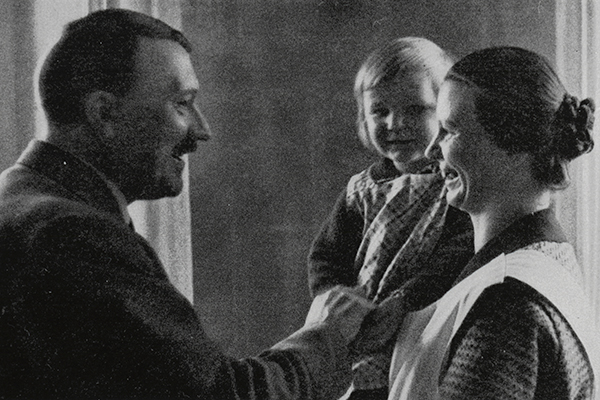"""Cigarette card titled """"Muttergluck"""" (Joy of Motherhood), which shows Adolf Hitler with a mother and child. US Holocaust Memorial Museum, courtesy of William O. McWorkman"""