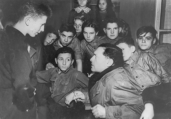 A journalist interviews residents of the Kloster Indersdorf children's center, which was established after the Holocaust by the United Nations Relief and Rehabilitation Administration to house non-German children who were orphaned or displaced. US Holocaust Memorial Museum, courtesy of Lilo, Jack, and Micha Plaschkes