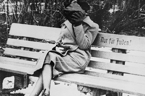 "Jewish woman sitting on a bench marked ""for Jews only,"" shortly after the Anschluss, the annexation of Austria into Nazi Germany in 1938. US Holocaust Memorial Museum, courtesy of The Wiener Library for the Study of the Holocaust & Genocide"