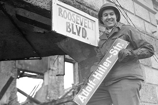 """Sergeant George A. Kaufman, an American soldier, replaces an """"Adolf Hitler"""" street sign in Krefeld, Germany, with a handmade one, """"Roosevelt Blvd,"""" March 1945. National Archives"""