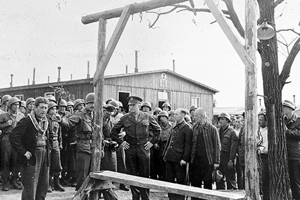 During a tour of the newly liberated Ohrdruf concentration camp in Germany, an Austrian Jewish survivor describes to General Dwight D. Eisenhower and his entourage the use of the gallows in the camp. National Archives