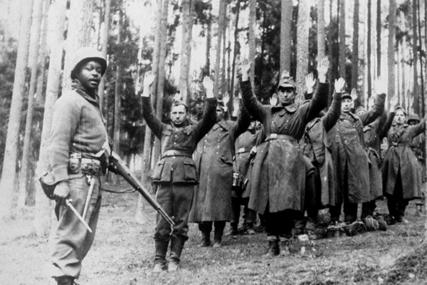 A Black soldier with the 12th Armored Division, Seventh US Army, stands guard over a group of German soldiers captured in the forest in April 1945. National Archives