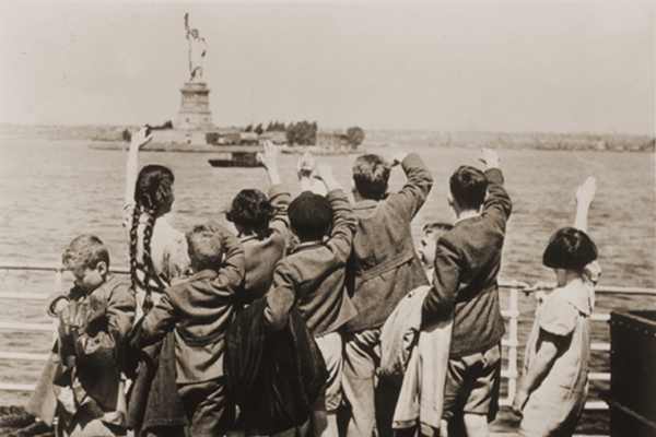 Austrian Jewish refugee children wave at the Statue of Liberty as the SS President Harding steams into New York harbor. US Holocaust Memorial Museum, courtesy of Anita Willens