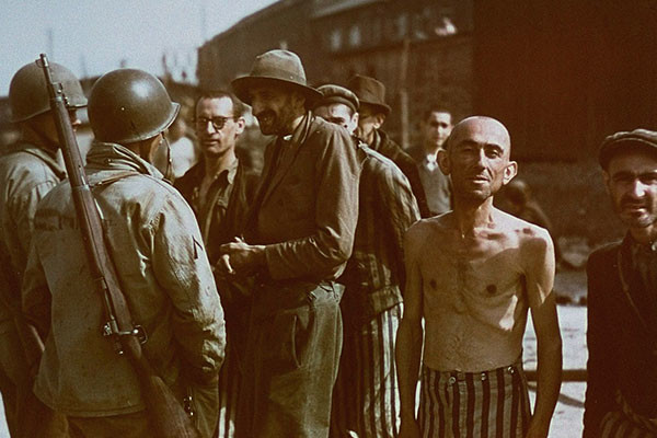 American soldiers speak with a group of survivors while on a tour of the Buchenwald concentration camp on April 18, 1945. National Archives and Records Administration