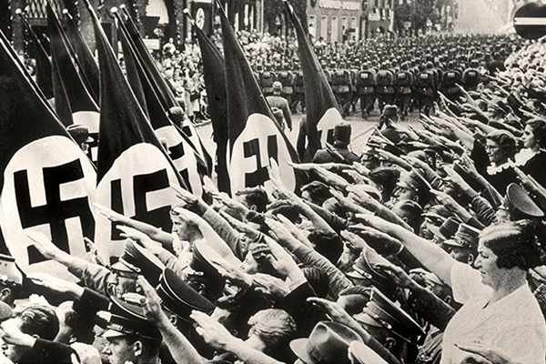 People salute Hitler while attending a Nazi Party parade in Nuremberg, Germany, 1937. Courtesy of Shawshots/Alamy Stock Photo