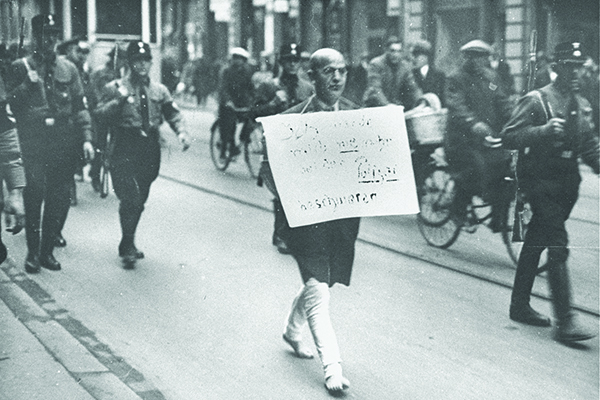 "Dr. Michael Siegel, a respected Jewish attorney from Munich, is forced to march barefoot through the streets with a sign around his neck that reads, ""I am a Jew, but I will never again complain to the police."" Bundesarchiv BILD 183-R99542"