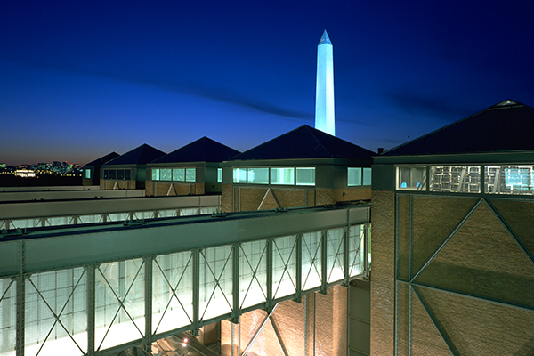 A nighttime view of the United States Holocaust Memorial Museum with the Washington Monument in the background. Timothy Hursley