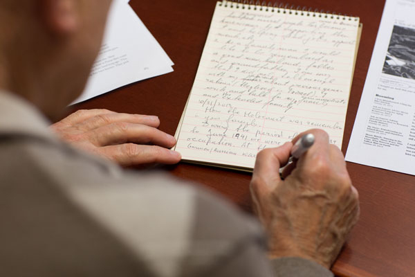 A Holocaust survivor pens a draft of his recollections during a Museum writers workshop, the Memory Project. Authors' works are published in volumes of Echoes of Memory. US Holocaust Memorial Museum